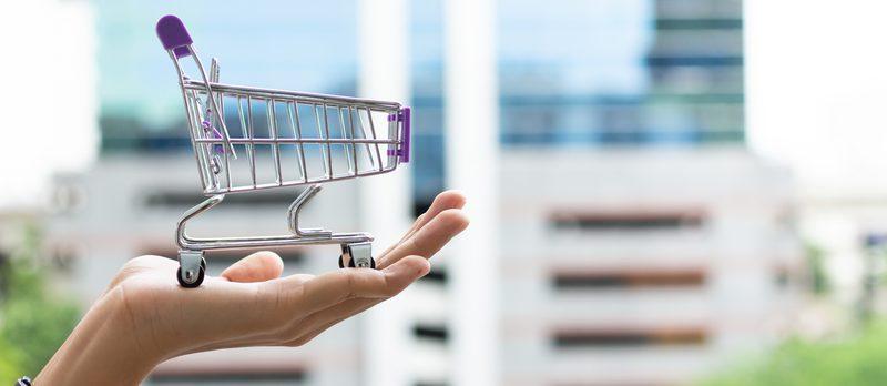 En hand håller en kundvagn, konceptbild webbutik.