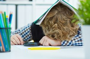 Tired schoolboy is sitting at a desk with head on the tablewith the notebook on the head. Large number of lessons and homework in the lower grades.