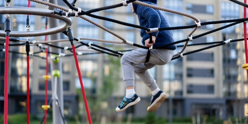a little boy is having fun playing on the modern urban European playground.