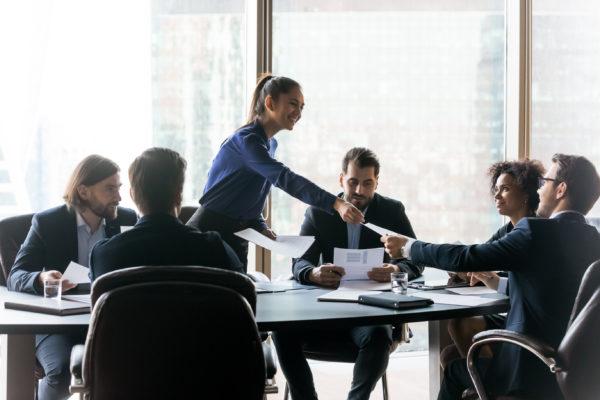 Ledare delar ut papper i samtalsgrupp